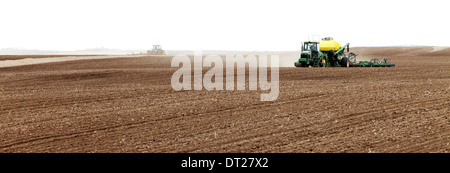 Tractors plowing and planting in a farm field - Stock Photo
