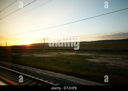 Sunset view of outskirts China on T22 Qinghai Tibet train - Stock Photo