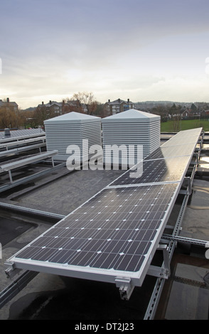 Photo-voltaic solar panels + 'windcatcher' ventilation units on the roof of a new school classroom block in Southeast - Stock Photo
