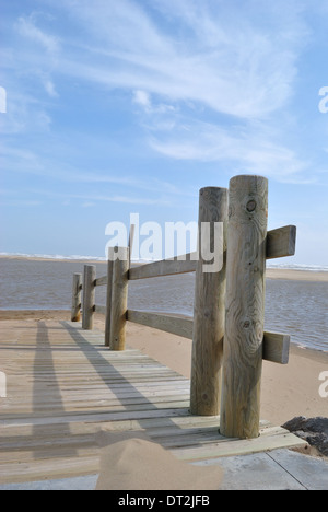 A wooden deck with wooden railing at the beach with blue sea and sky in Gruissan Plage. - Stock Photo