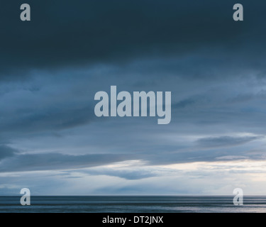 The sea and sky over Puget Sound in Washington USA The horizon with light and cloud layers above Gathering storm - Stock Photo