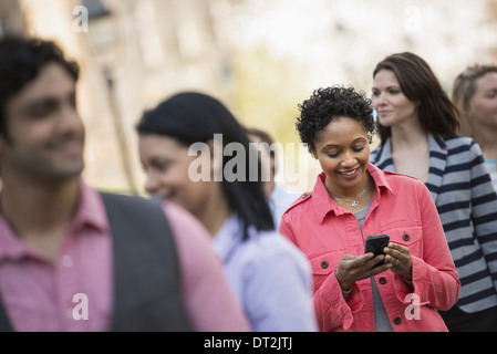 People outdoors in the city in spring time A woman standing among a group checking her cell phone - Stock Photo