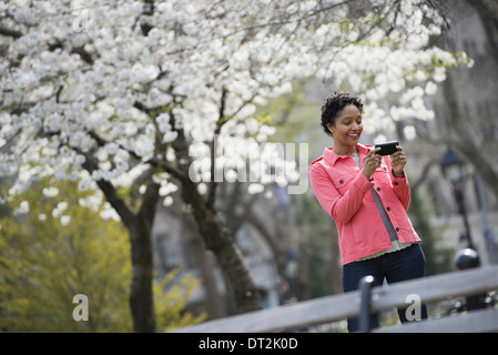 Outdoors in the city in spring time New York City park White blossom on the trees A woman holding her mobile phone and smiling