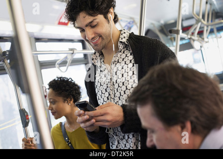New York City park People men and women on a city bus Public transport Keeping in touch A young man checking his - Stock Photo