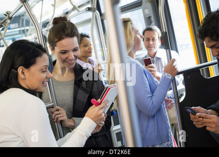 New York City People men and women on a city bus Public transport Two women looking at a handheld digital tablet - Stock Photo