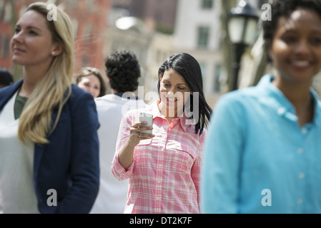 park Three women one checking her mobile phon - Stock Photo