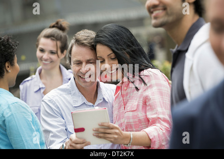 People outdoors spring time New York City a couple in the centre looking at a digital tablet screen - Stock Photo