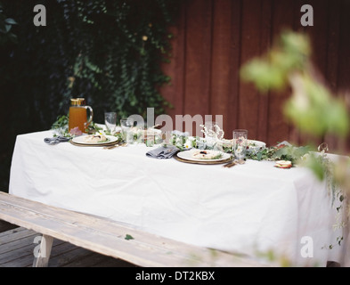 A table laid for a special meal Place settings with plates and cutlery Glasses A white table cloth and bench seat - Stock Photo