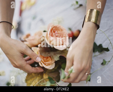 A woman arranging fresh flowers on a tabletop covered with a white cloth Peach coloured roses Stock Photo