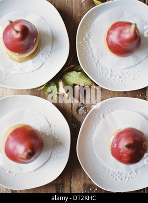 Tabletop viewed from above Four plates with dessert Pears dipped in sauce - Stock Photo