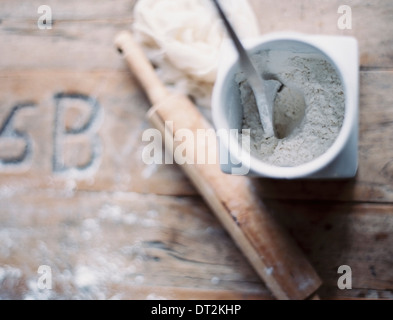 A domestic kitchen A small group of objects A rolling pin and jar of flour on a worn tabletop View from above Stock Photo