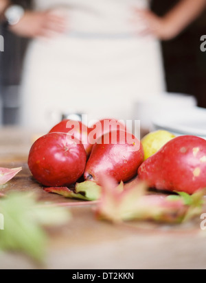 A domestic kitchen tabletop A small group of fresh organic pears and a stack of white plates Stock Photo