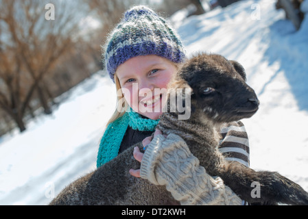 Winter scenery with snow on the ground A young girl holding a young lamb - Stock Photo