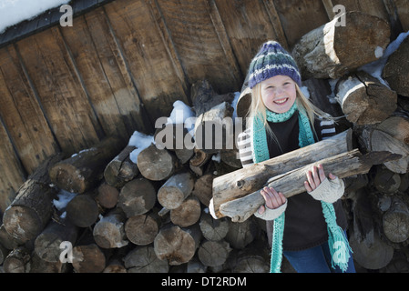 Winter scenery with snow on the ground A girl collecting firewood from the log pile - Stock Photo