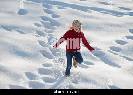Winter scenery with snow on the ground A young girl running through deep snow making footprint tracks - Stock Photo