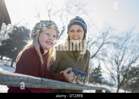 Winter scenery with snow on the ground A child and an adult having a hot drink on a cold day - Stock Photo