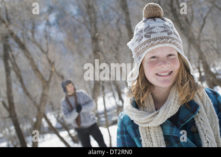 Winter scenery with snow on the ground A young girl with a bobble hat and scarf outdoors A man in the background - Stock Photo