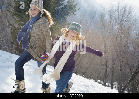 Winter scenery with snow on the ground A woman and a child hand in hand running across the snow - Stock Photo