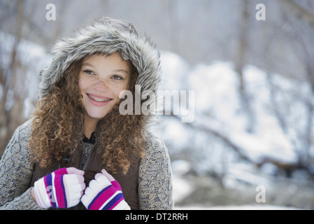 Winter scenery with snow on the ground A young girl in a woolly hat with ski gloves on - Stock Photo