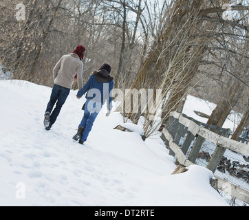 Winter scenery with snow on the ground A couple walking hand in hand along a path - Stock Photo