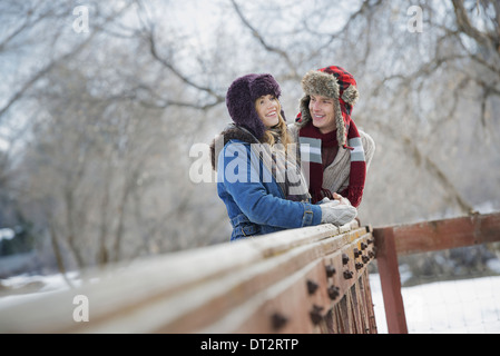 Winter scenery with snow on the ground A couple young man and young woman leaning on a fence - Stock Photo