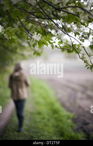 A woman in a brown hooded coat and hat walking along a path beside a ploughed field - Stock Photo