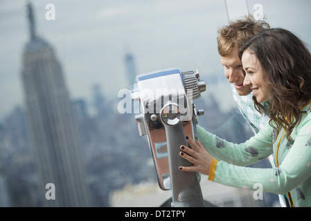 View over cityA young couple looking through the telescope - Stock Photo