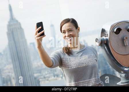 View over cityA woman using her smart phone to photograph the view - Stock Photo