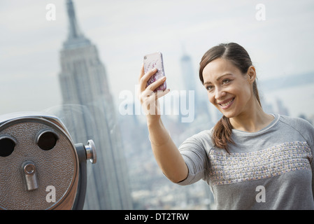 View over cityA woman using her smart phone to take a photograph - Stock Photo