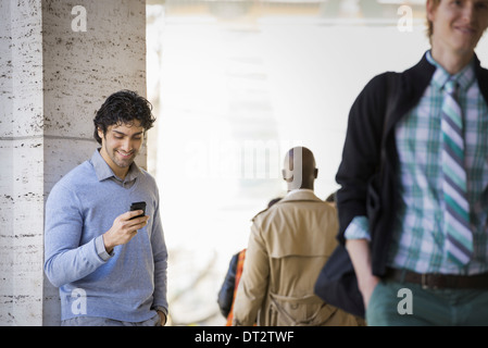 Three people on the sidewalk a man using his mobile phone a man in a raincoat and a young man walking along the - Stock Photo