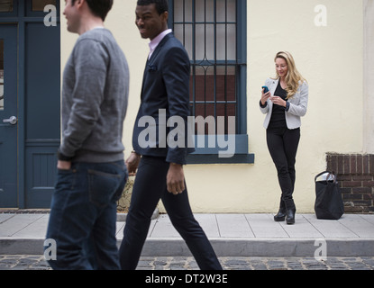 Young people outdoors on the city streets in springtime A woman on her own and two men walking past on the cobbled - Stock Photo