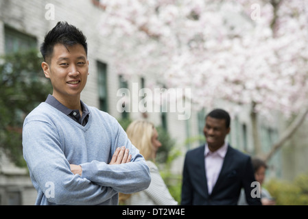 View over cityA man with his arms folded and two people talking in the background under the trees in blossom