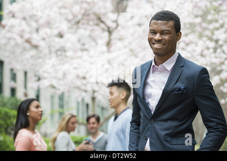 Young people outdoors in a city park A man in a suit smiling Four people in the background Using cell phones - Stock Photo