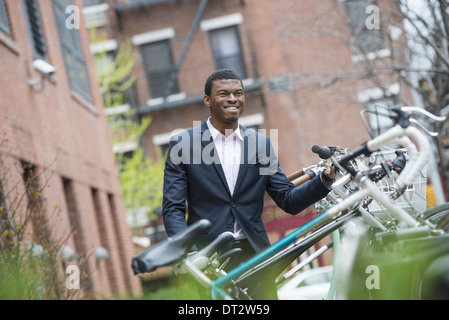 View over cityA man in a blue suit by a bicycle rack in a city park - Stock Photo