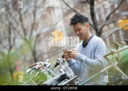 View over cityA man in a blue sweater by a row of parked bicycles Checking his messages on a smart phone - Stock Photo