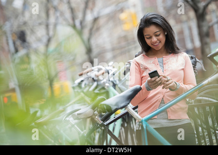 View over cityA young woman in a peach coloured shirt using her smart phone Bicycles parked in a bike rack - Stock Photo