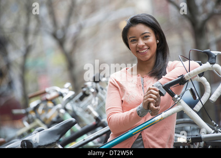 View over cityA young woman with black hair wearing a peach shirt standing beside a rack of parked locked bicycles - Stock Photo