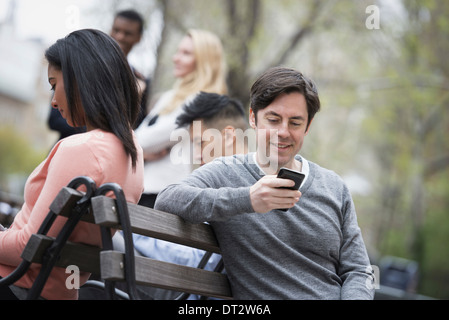 View over citycity park Sitting on a park bench Five people men and women checking their phones - Stock Photo
