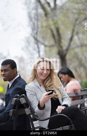 View over cityYoung people outdoors in a city park Three people sitting on a bench Two checking their phones - Stock Photo