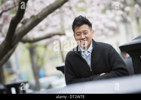 View over cityA young man outdoors in a city park Sitting on a bench - Stock Photo
