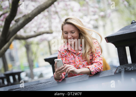 View over cityA young woman with long blonde hair sitting in a city park looking at her smart phone - Stock Photo