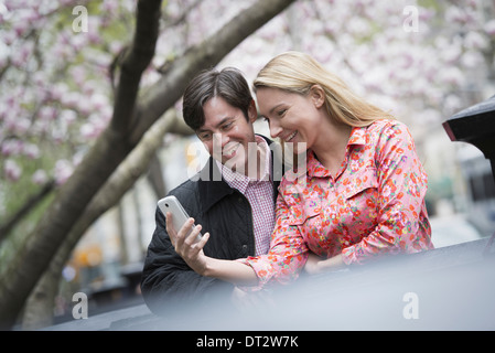 View over cityYoung people outdoors park A young woman and man sitting side by side looking down at a smart phone - Stock Photo