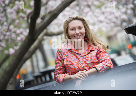 View over cityA young woman with long blonde hair outdoors in a city park - Stock Photo