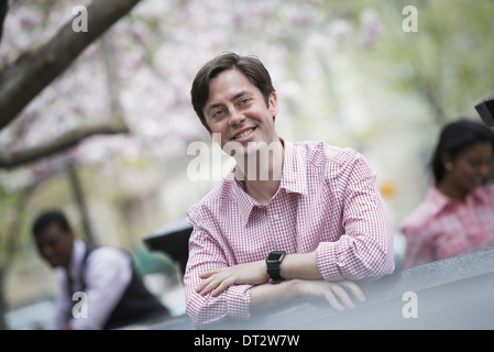 View over cityA man sitting outdoors in a city park Looking at the camera and smiling - Stock Photo