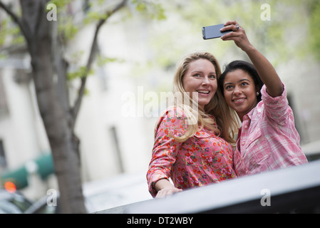 View over cityYoung people outdoors in a city park Two women taking a self portrait or selfy with a smart phone - Stock Photo