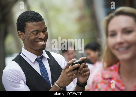 View over cityin a park A man smiling as he looks at his phone and a close of up of a woman with blonde hair - Stock Photo