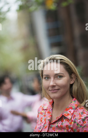 View over cityA woman with long blonde hair looking at the camera - Stock Photo