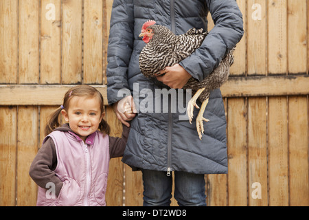 A woman holding a black and white chicken with a red coxcomb under one arm A young girl beside her holding her other - Stock Photo
