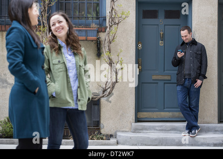 Two women talking as they walk down a street A man leaning against a house door checking his phone - Stock Photo