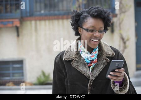 A woman wearing glasses looking at her smart phone keeping in touch while on the go - Stock Photo